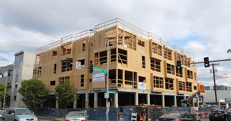 Photograph of a three-story wood apartment building being constructed about a concrete podium in Seattle.