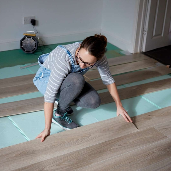 Woman laying new wood flooring.