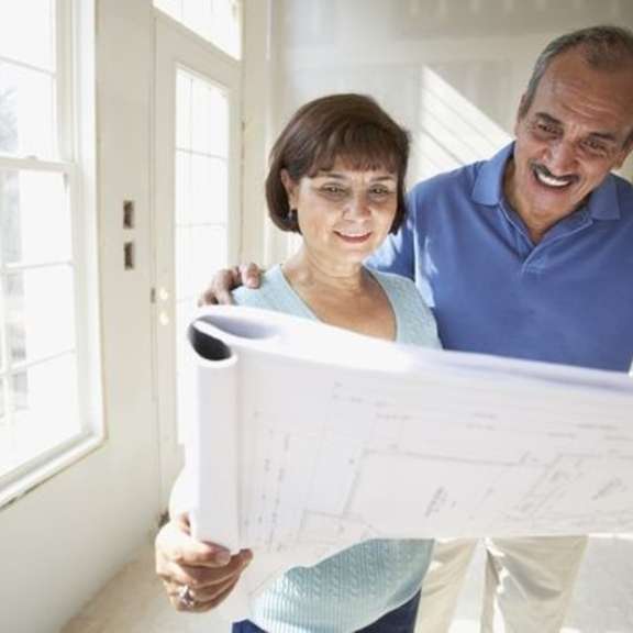 Man and woman considering floor plans.